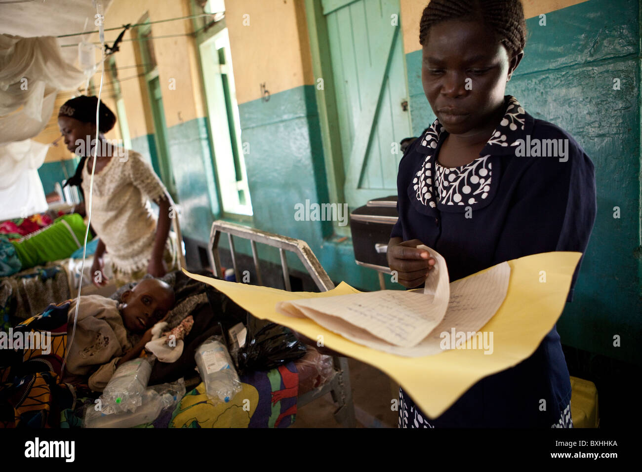 A doctor looks over the records of a child dying of AIDS in a hosptial in Amuria, Uganda, East Africa. - Stock Image