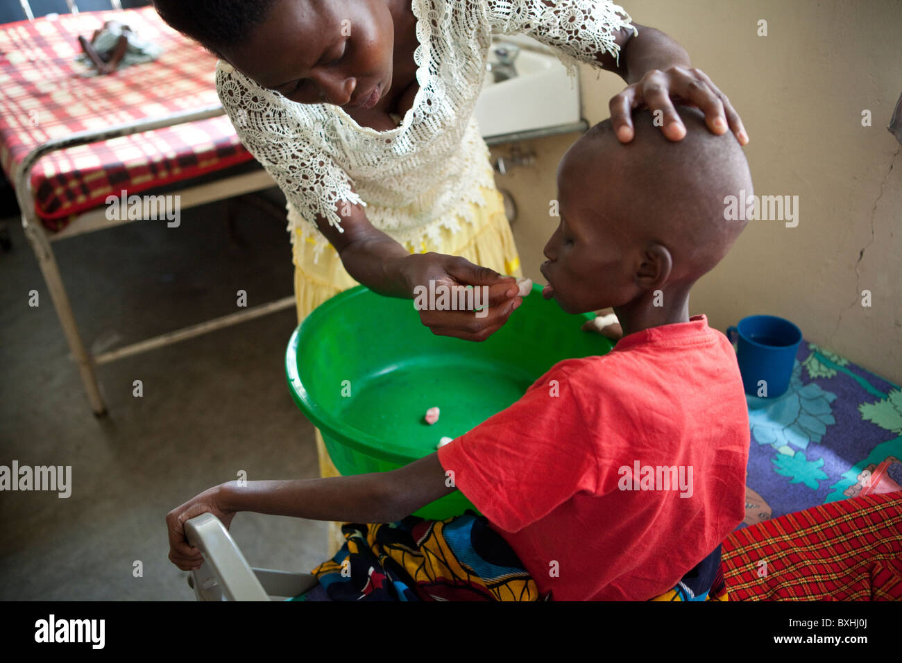 A woman cares for her daughter dying of AIDS in Soroti, Uganda, East Africa. - Stock Image