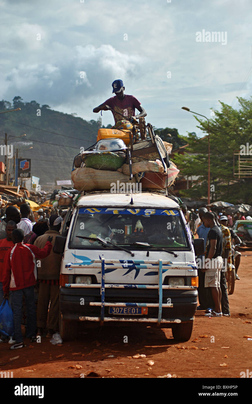 Man loading up a minibus in the Ivory Coast, West Africa - Stock Image