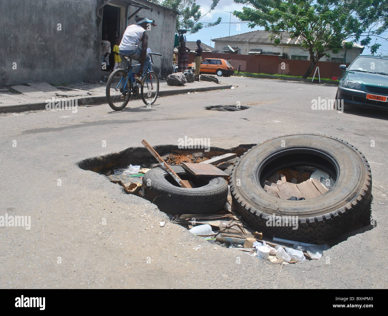 Giant potholes in a road in Abidjan, Ivory Coast - Stock Image