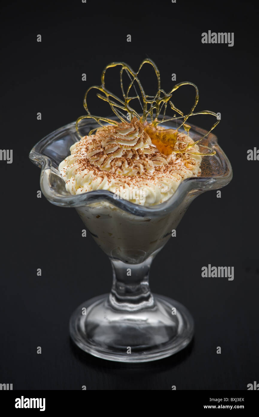 ice cream in glass bowl dusted with chocolate and decorated with caramel curl - Stock Image