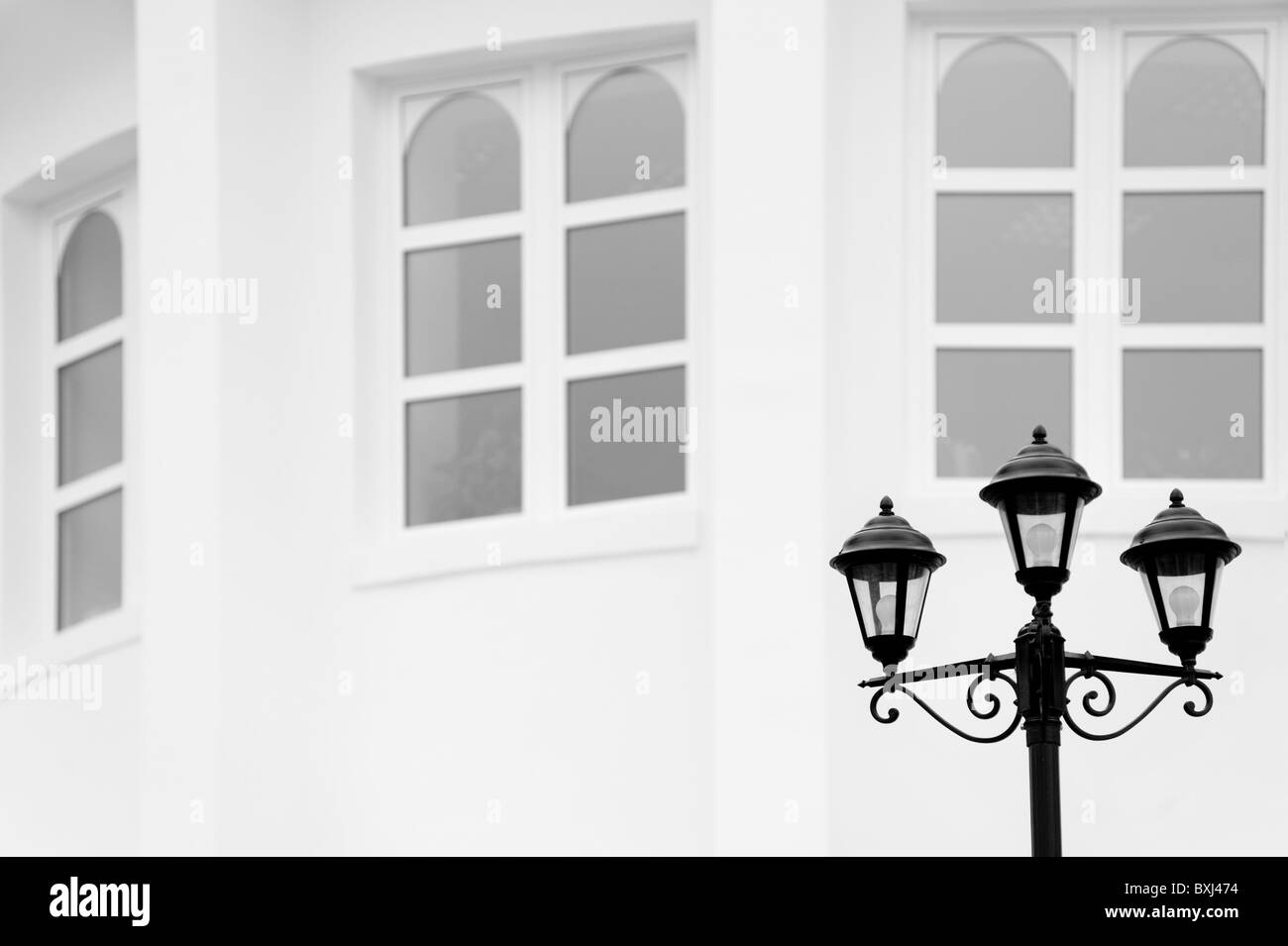 antiqued forged black street lamp against white wall with three windows - Stock Image