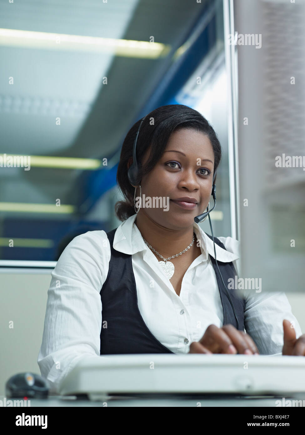 female african american customer service representative talking on the phone and typing on pc. Vertical shape, front Stock Photo