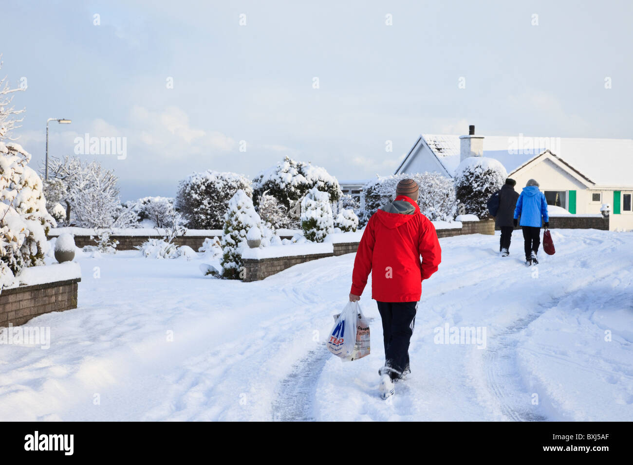 Snow scene with people carrying shopping along residential street on a cold winter's day after heavy snowfall - Stock Image