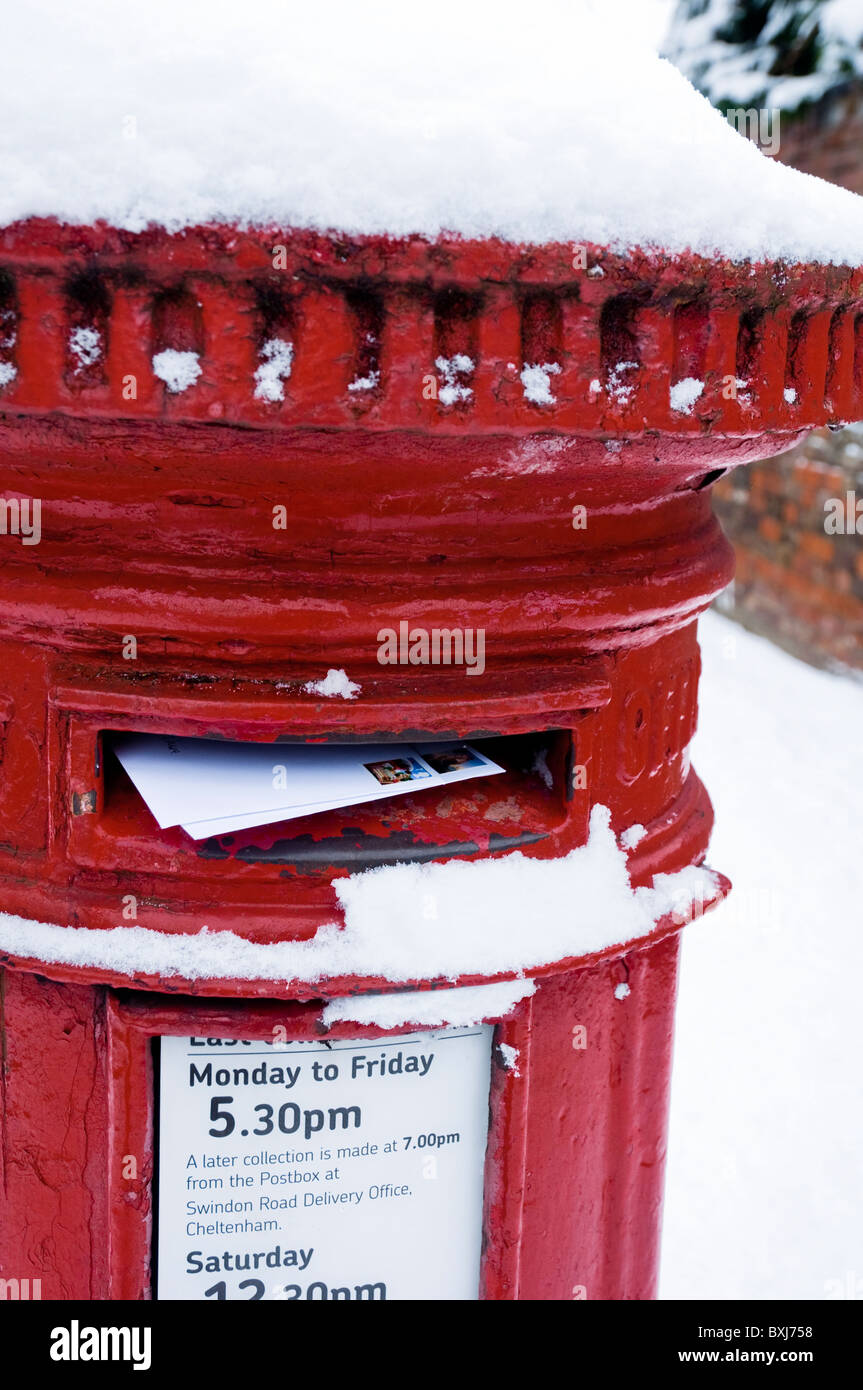 Posting letters / christmas cards into a red letter box covered with snow. UK - Stock Image