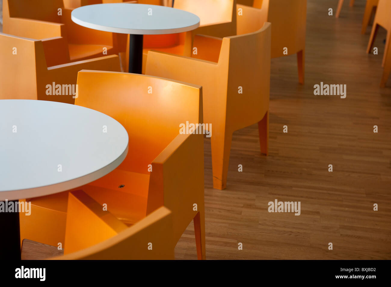 orange plastic polypropylene philippe starck toy chairs in a cafe