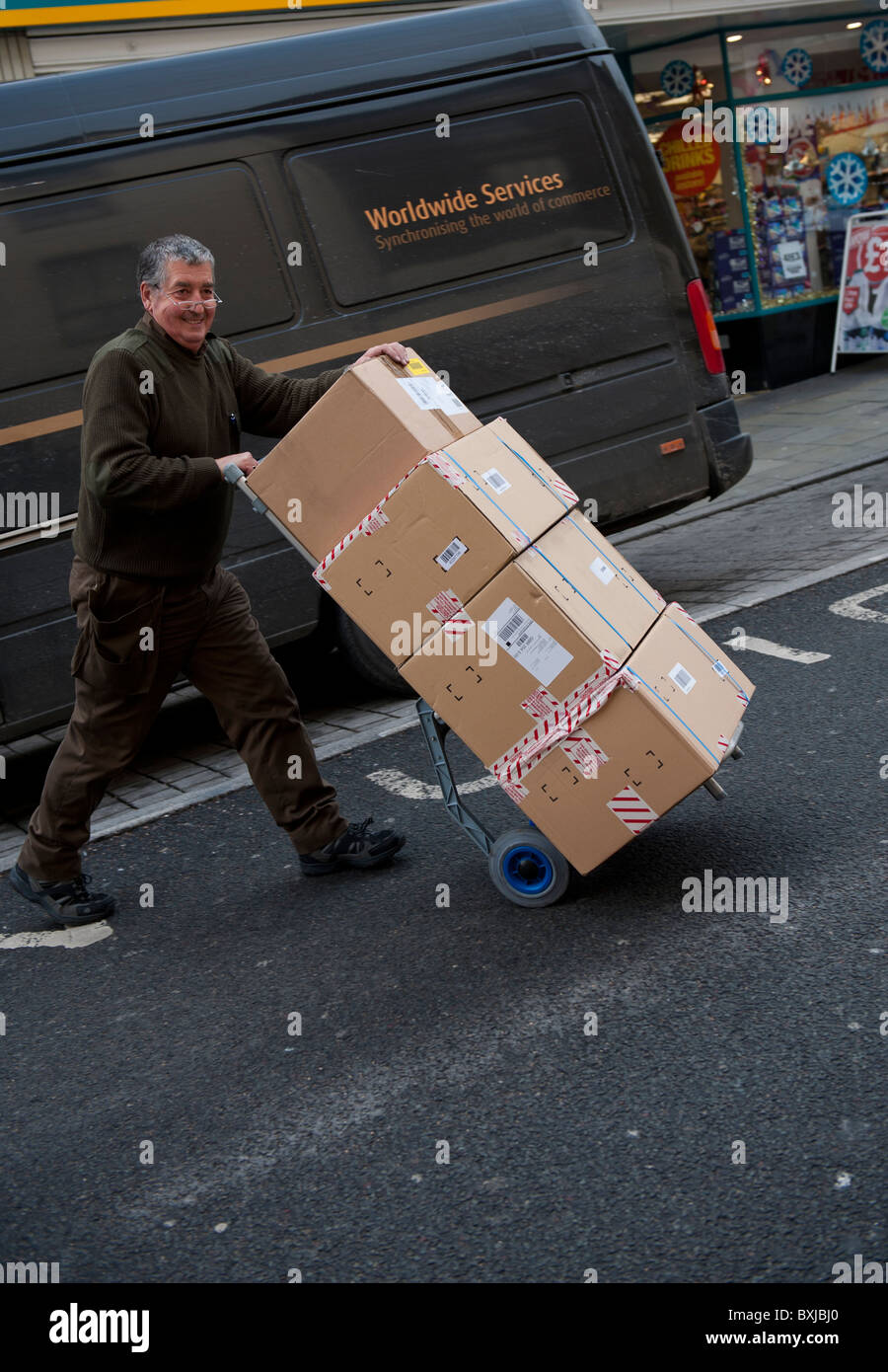 A UPS United Parcels Service courier service man delivering a stack of parcels to a customer, UK - Stock Image