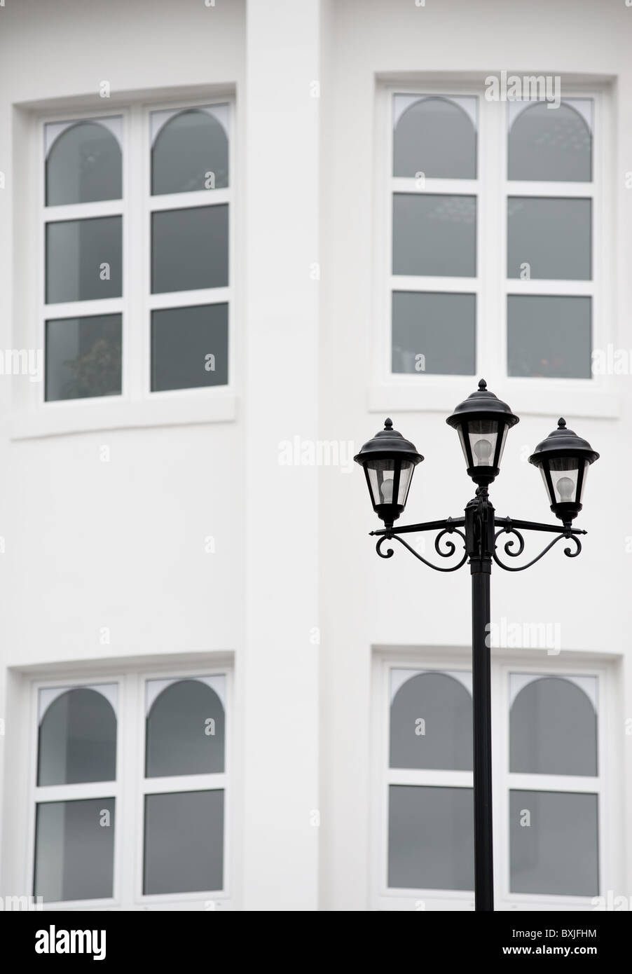 antiqued forged black street lamp against white wall with four arched windows - Stock Image