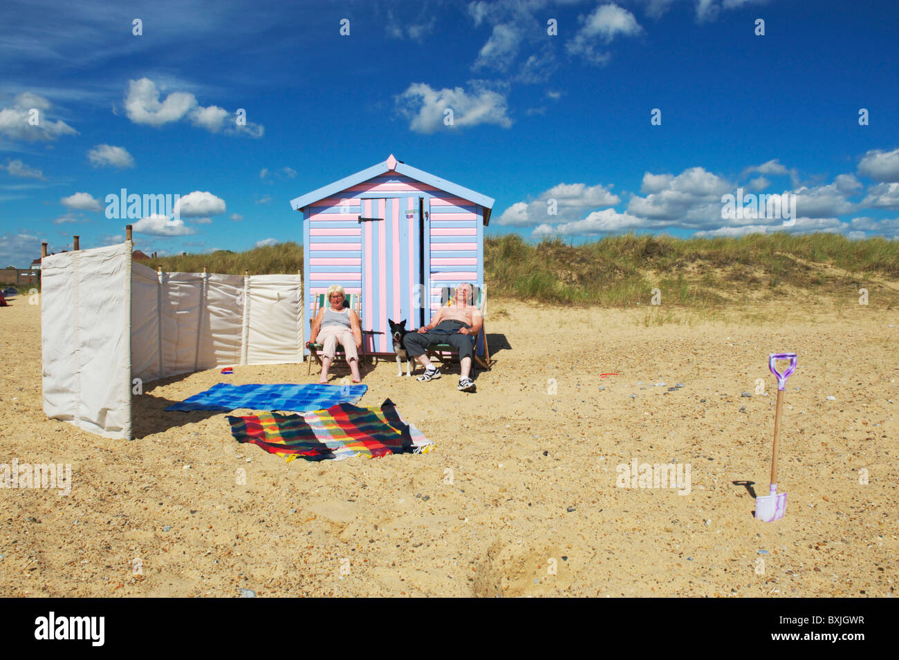 two elderly holidaymakers enjoy sitting in the sun outside a beach hut in Great Yarmouth - Stock Image