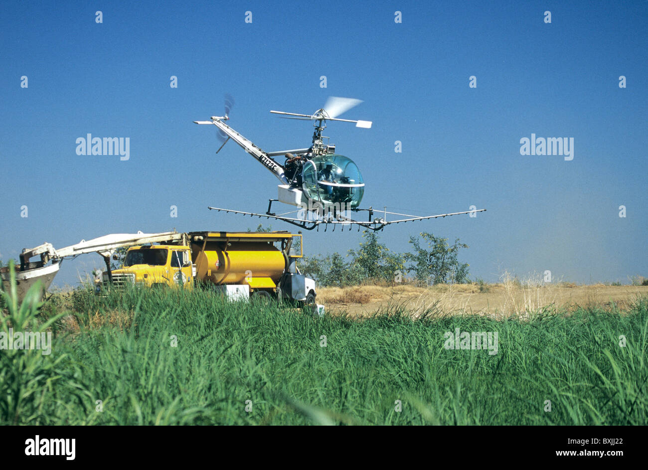 Rice field, helicopter departing from truck mounted service platform, - Stock Image