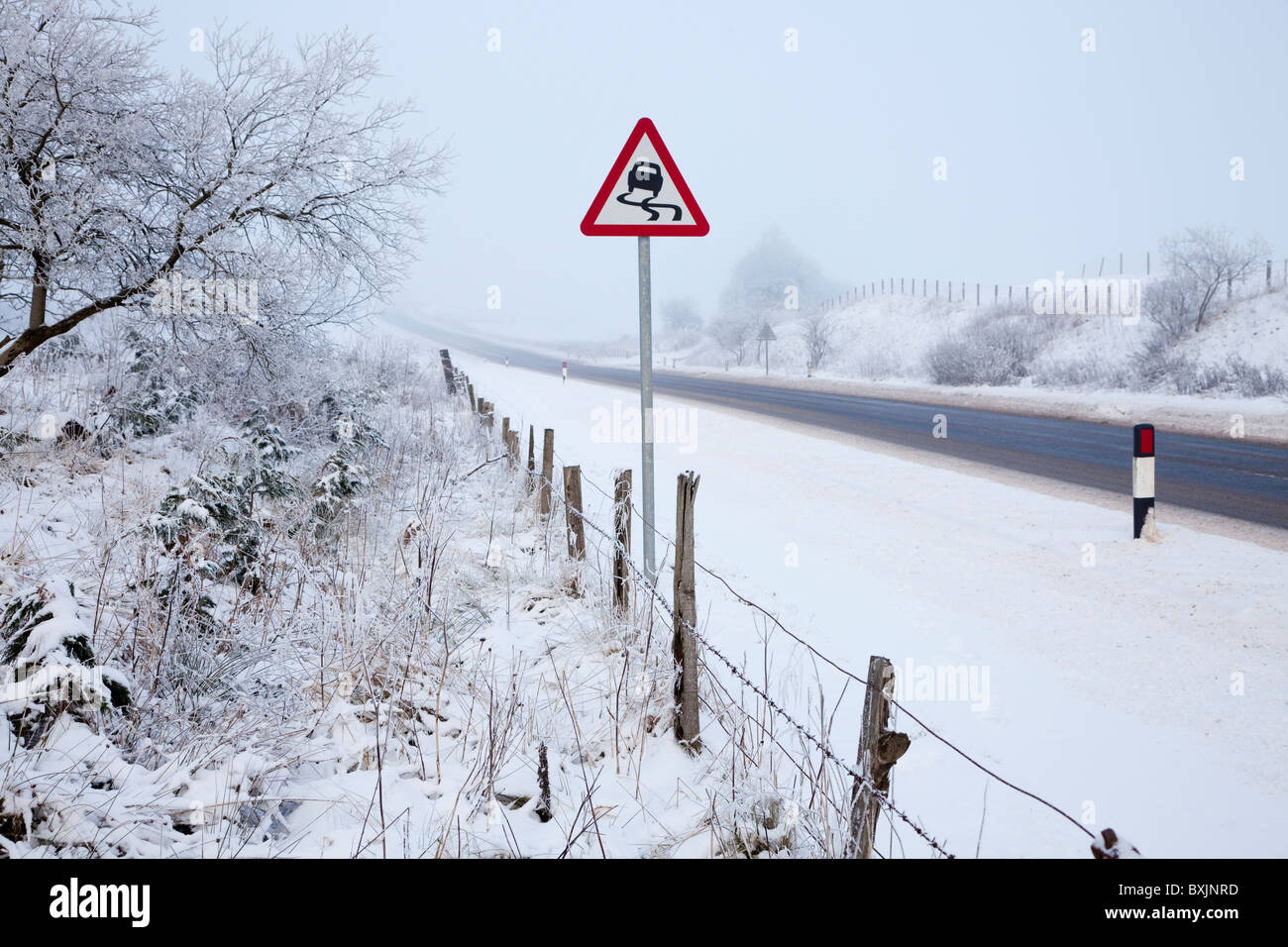 Winter road with freezing fog, snow and warning sign, near Floak on the road to Glasgow, Ayrshire, Scotland - Stock Image