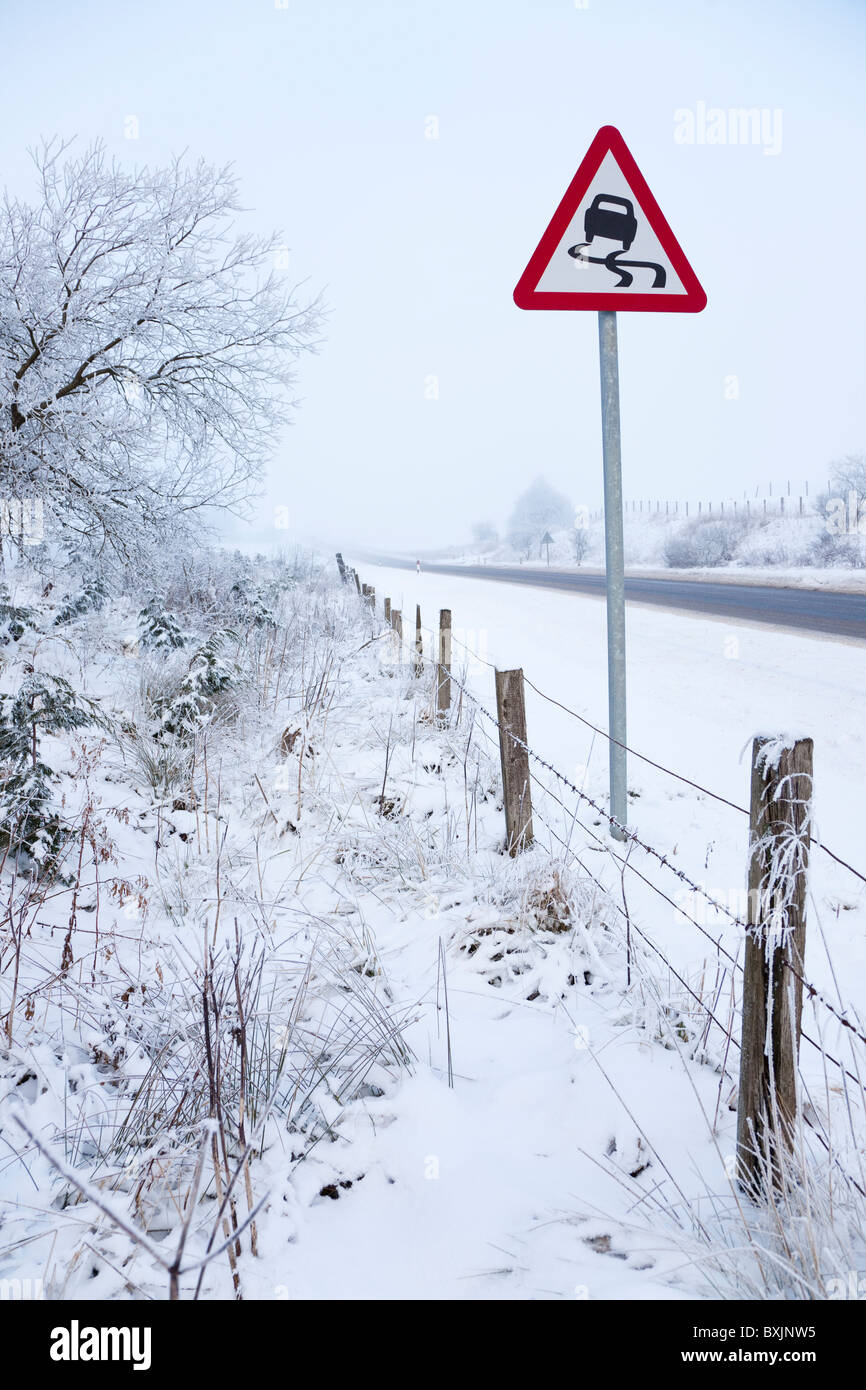 Winter road with freezing fog, snow and warning sign near Floak on the road between Kilmarnock and Glasgow, Scotland - Stock Image