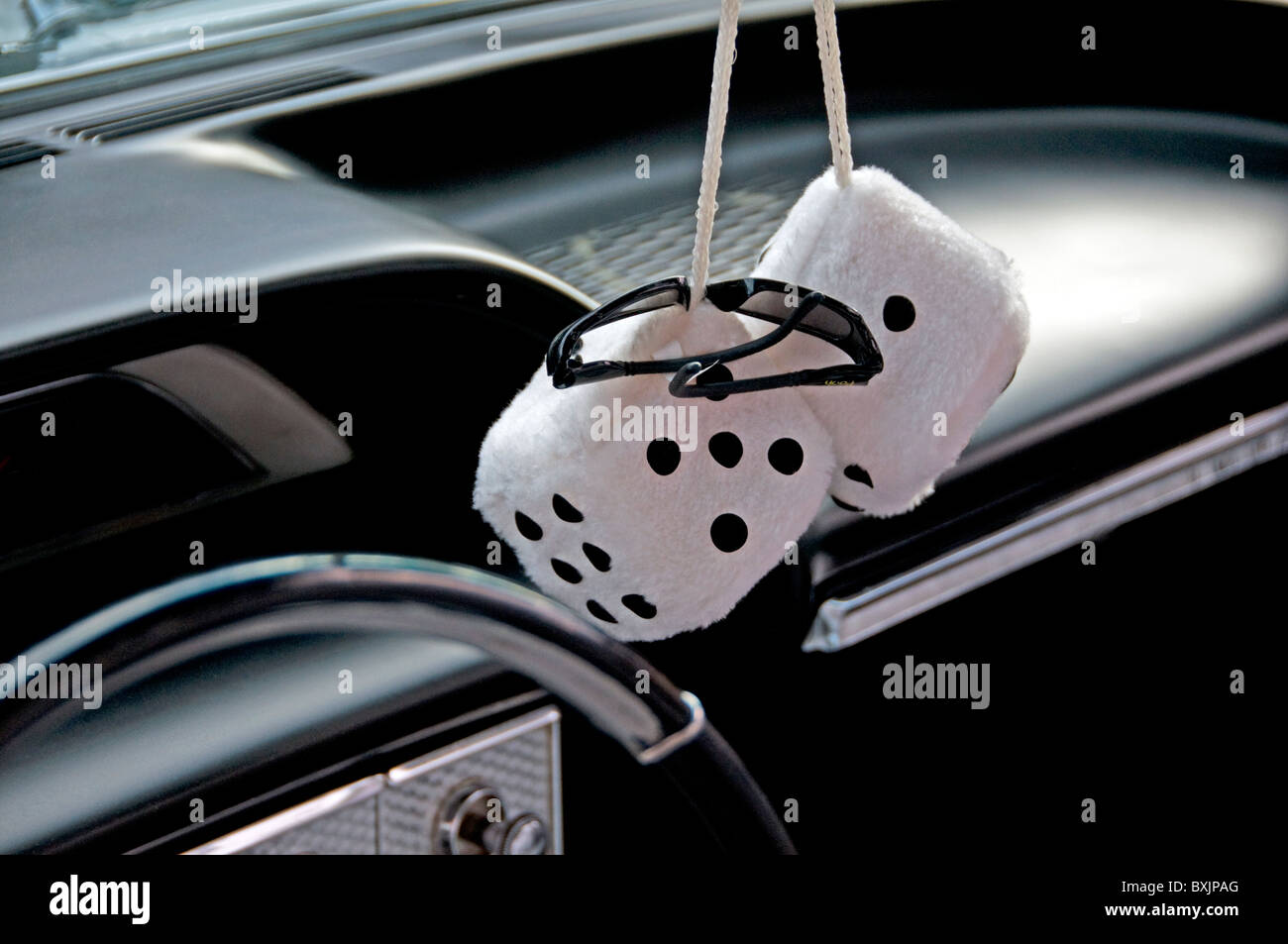 Fuzzy dice hanging on rear view mirror - Stock Image