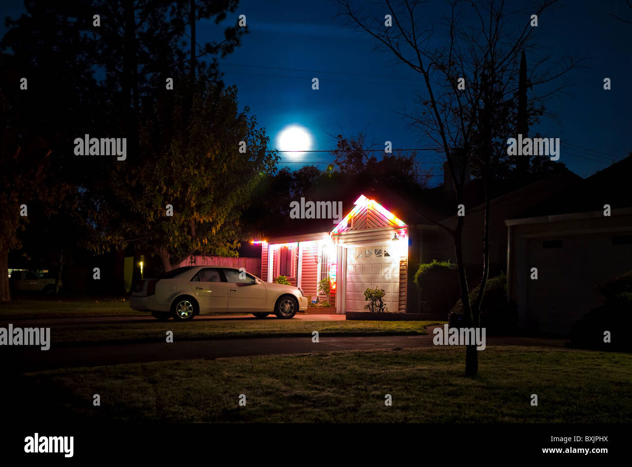 Moon shines above a house decorated with Christmas lights Stock Photo