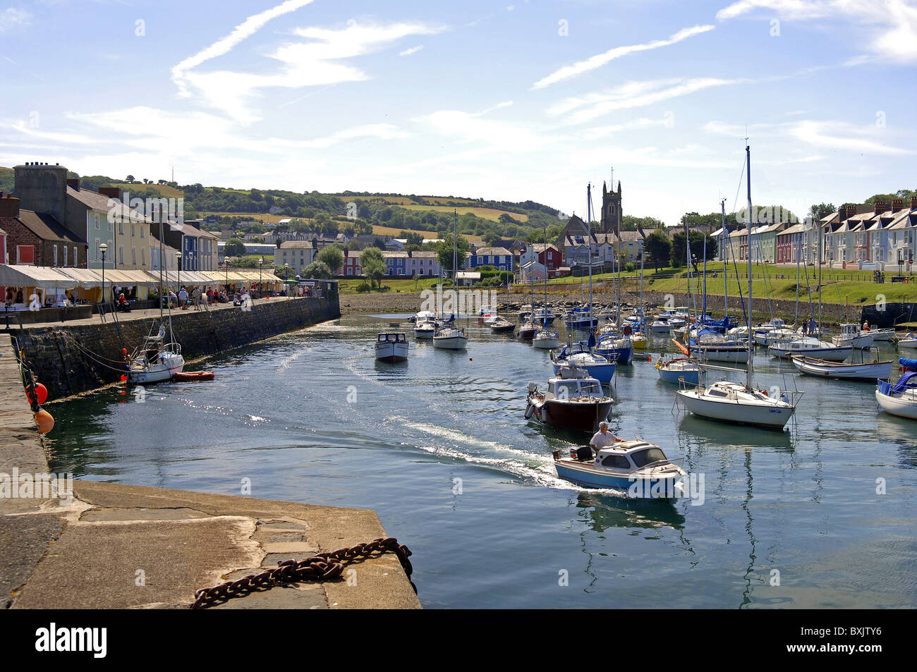 a boat leaves the harbor in aberaeron during the seafood festival - Stock Image