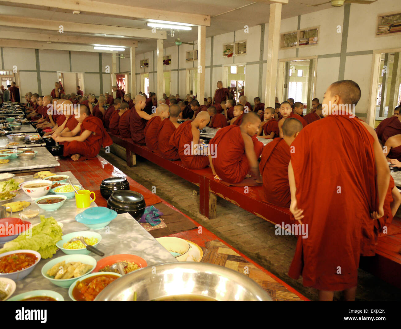 Monks sitting down for lunch at Amarapura Monastry, near Mandalay - Stock Image