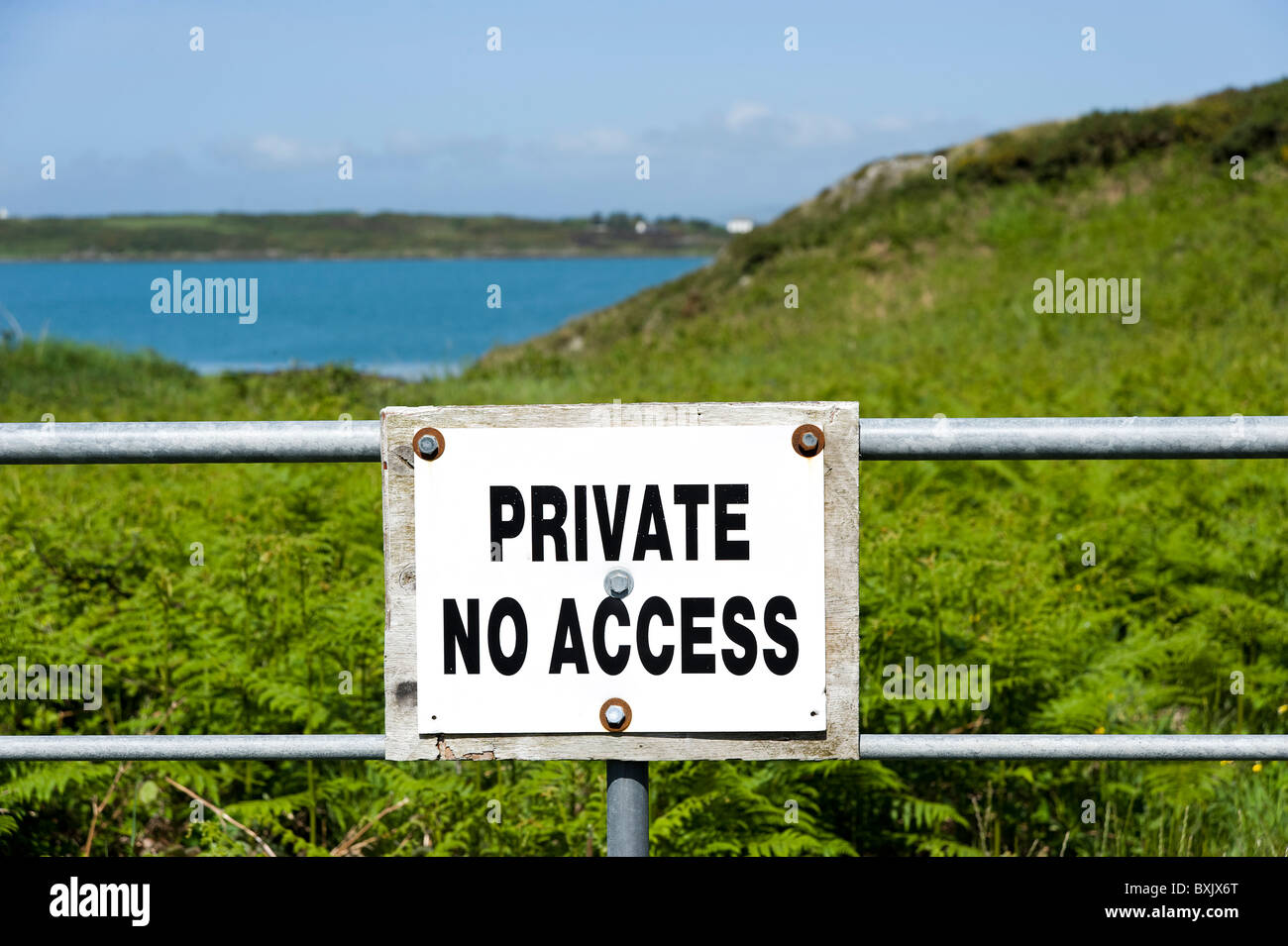 Private No Access sign across barrier on coastal land on Sherkin Island, County Cork, Ireland - Stock Image