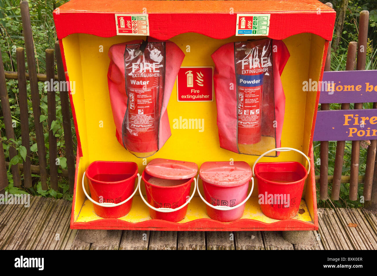 Fire extinguishers and water and sand buckets at Bewilderwood adventure park in Hoveton , Norfolk , England , Great - Stock Image