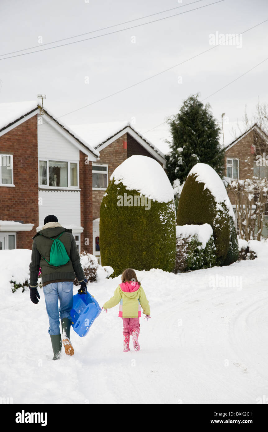 A father and daughter walking home in the snow after tobogganing / sledging - Stock Image