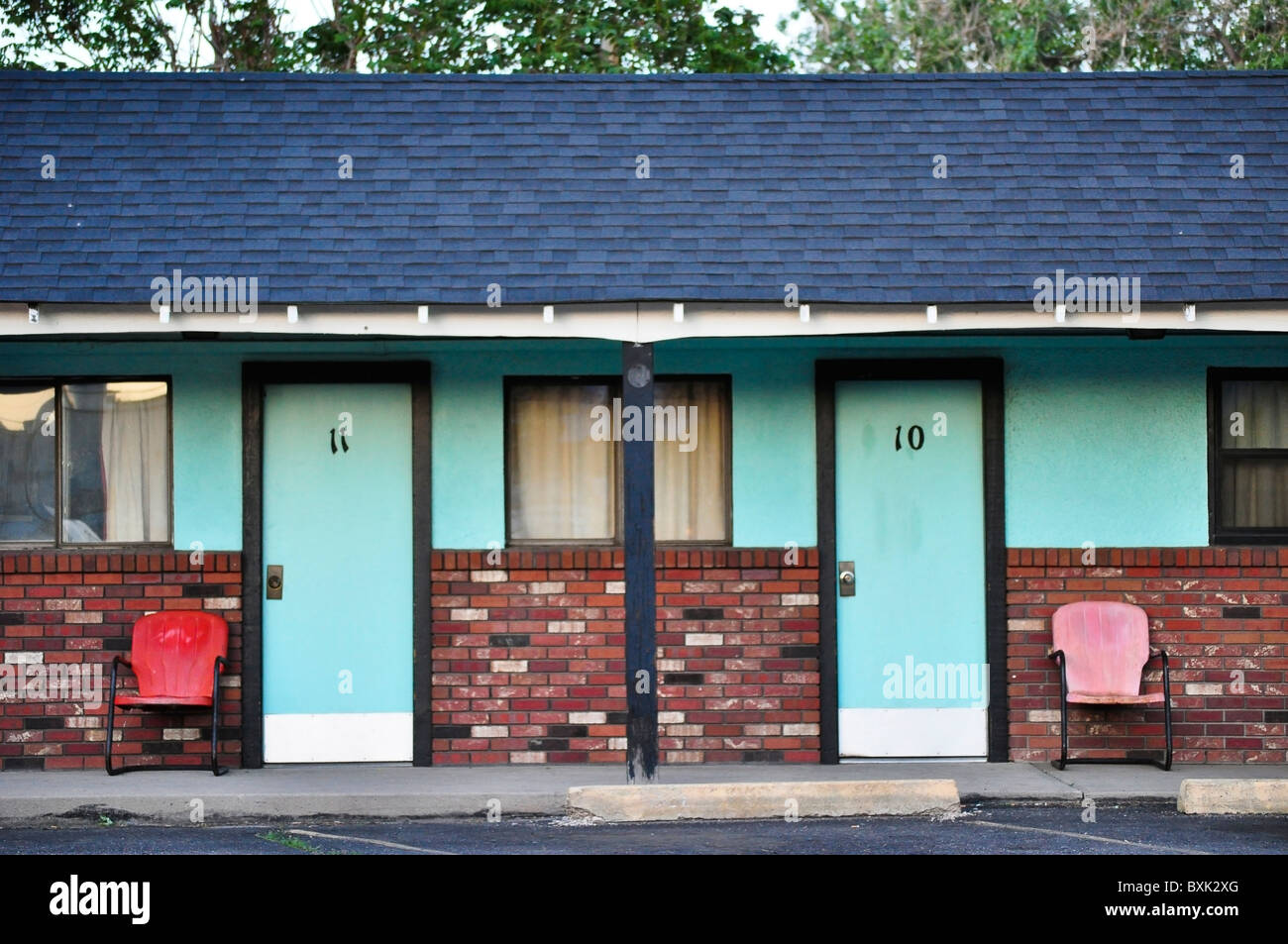 old motel with doors and colorful chairs - Stock Image