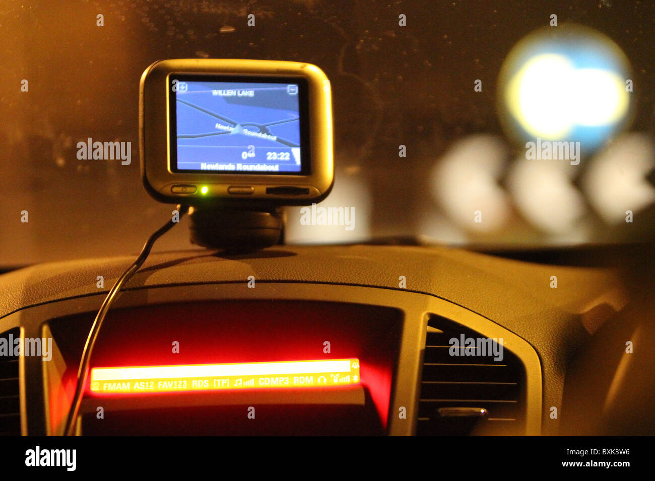 Sat Nav unit perched on a car's dashboard at night - Stock Image