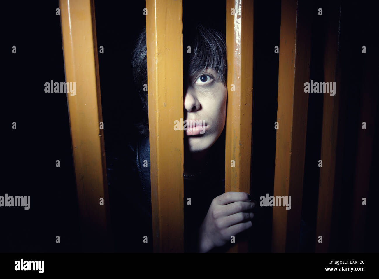 Afraid young man hiding in the dark interior. Natural lights and shadows - Stock Image
