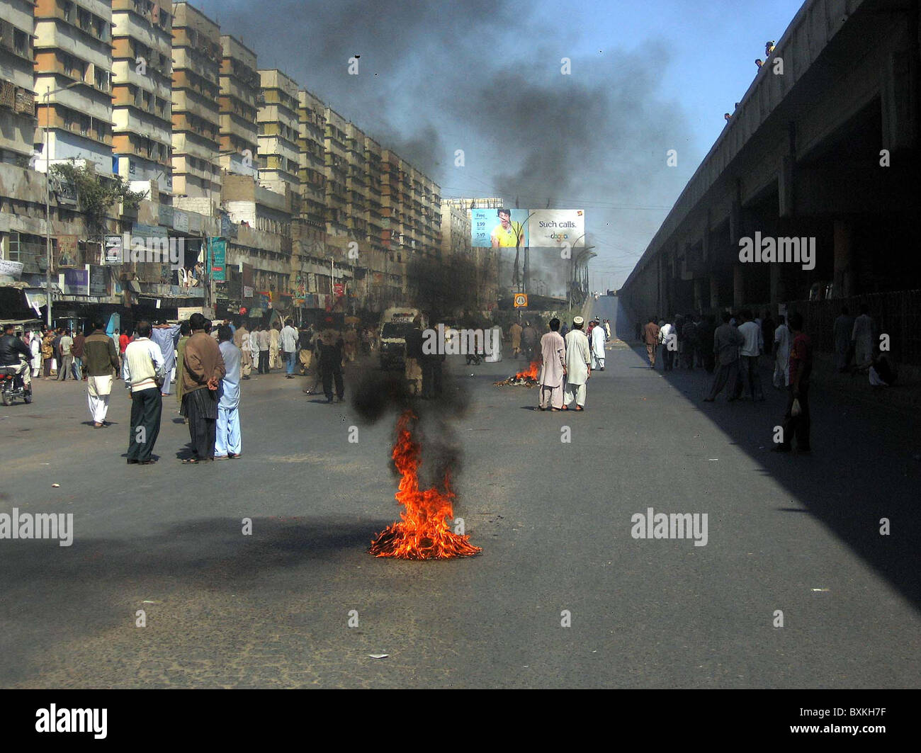 Residents of Liaquatabad stand near burning tyres as they are protesting against disconnection of the electricity - Stock Image