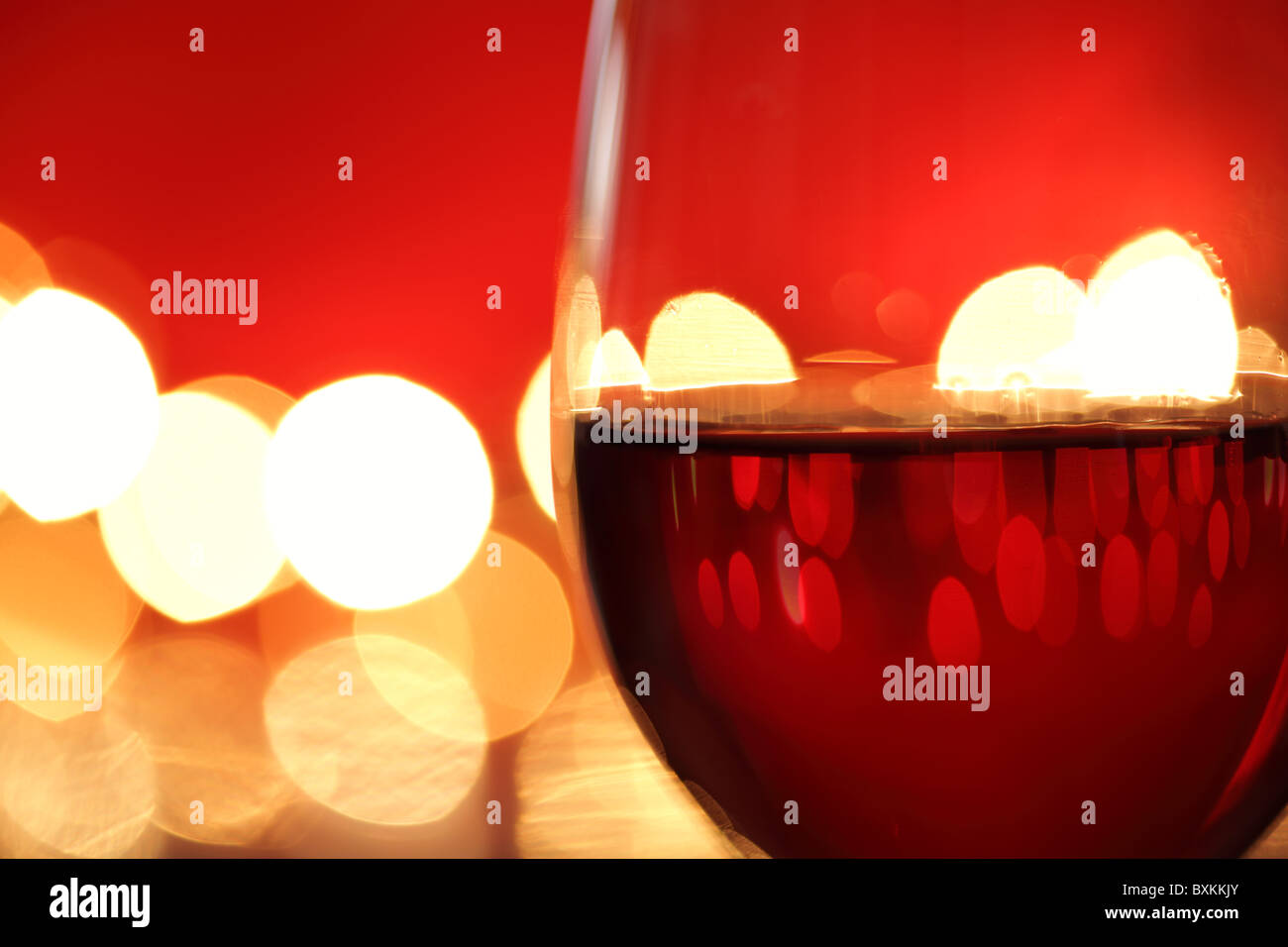 Glass of red wine against defocussed lights - Stock Image
