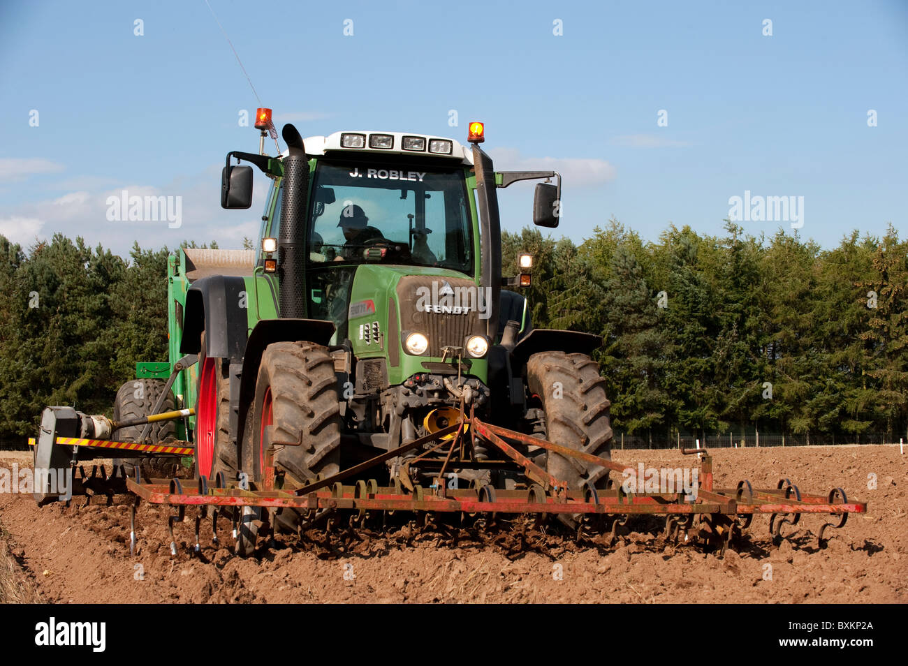 Fendt 716 tractor with stone picker going over newly ploughed field. - Stock Image