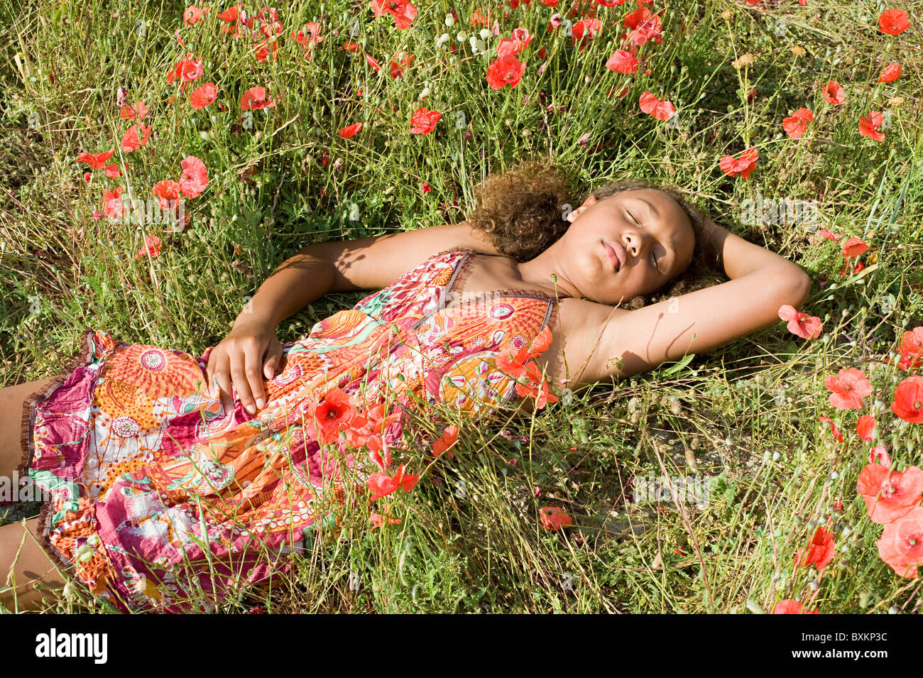 Young girl lying in poppy field - Stock Image