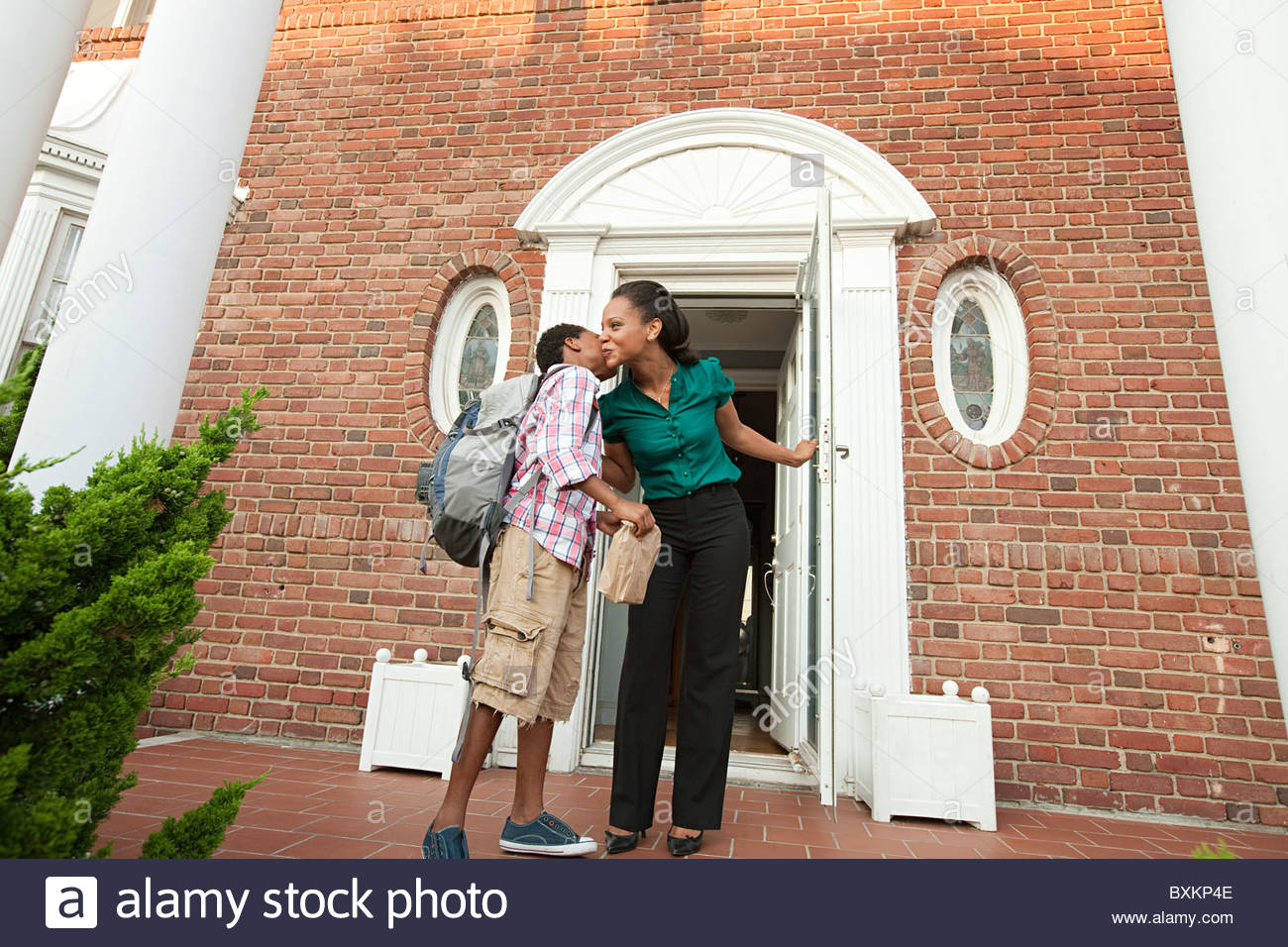 Mother sending son off with packed lunch in the morning - Stock Image