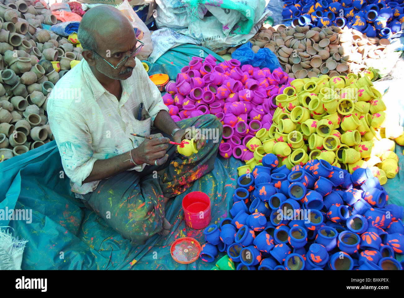 Artisan painting earthen pots. These pots are used in Diwali - Stock Image