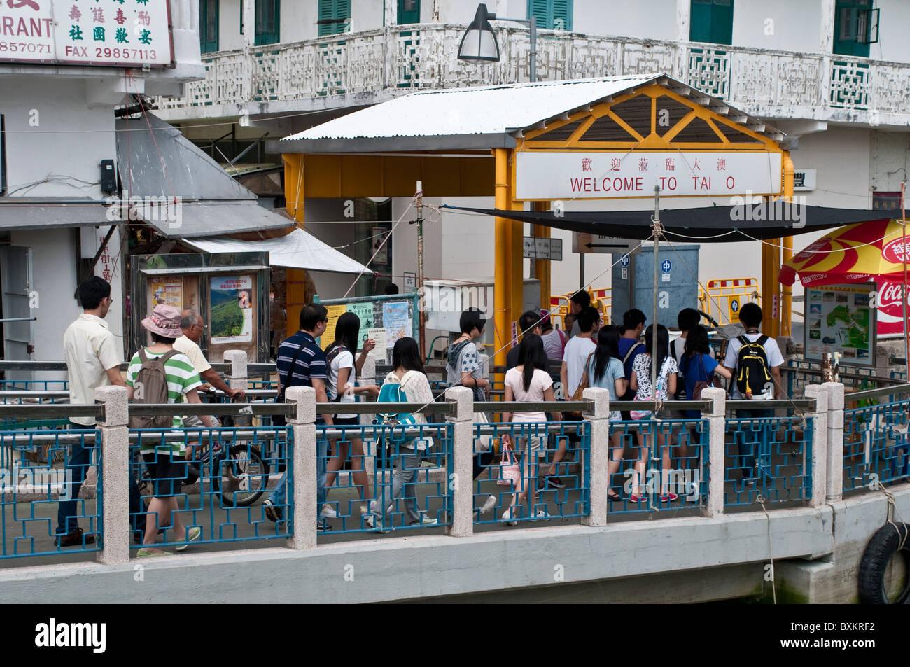 Tourists crossing the Bridge in Tai O village, Lantau island, Hong Kong, China - Stock Image