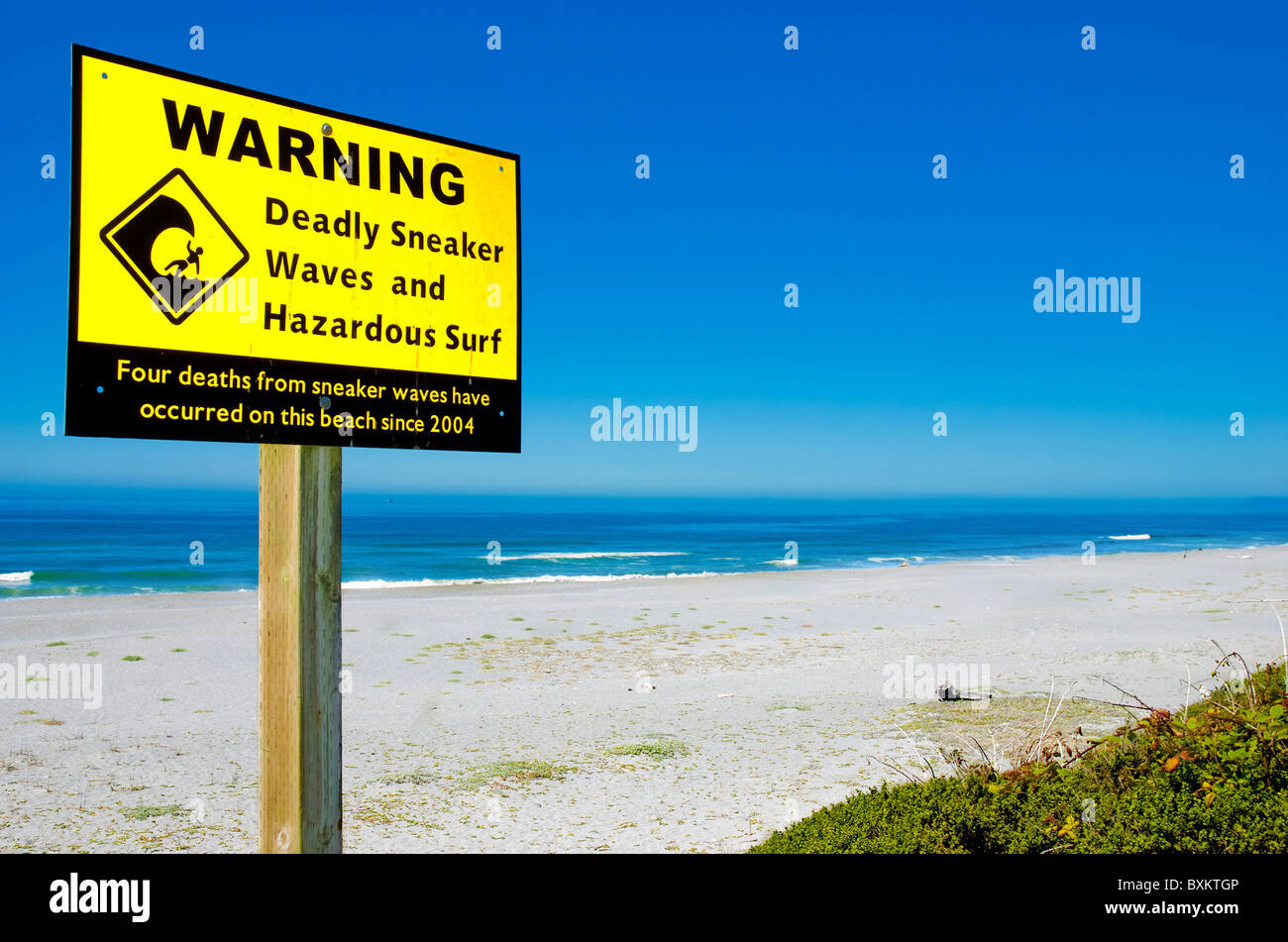 Sign warning of sneaker waves and hazardous surf on Pacific Coast Stock Photo