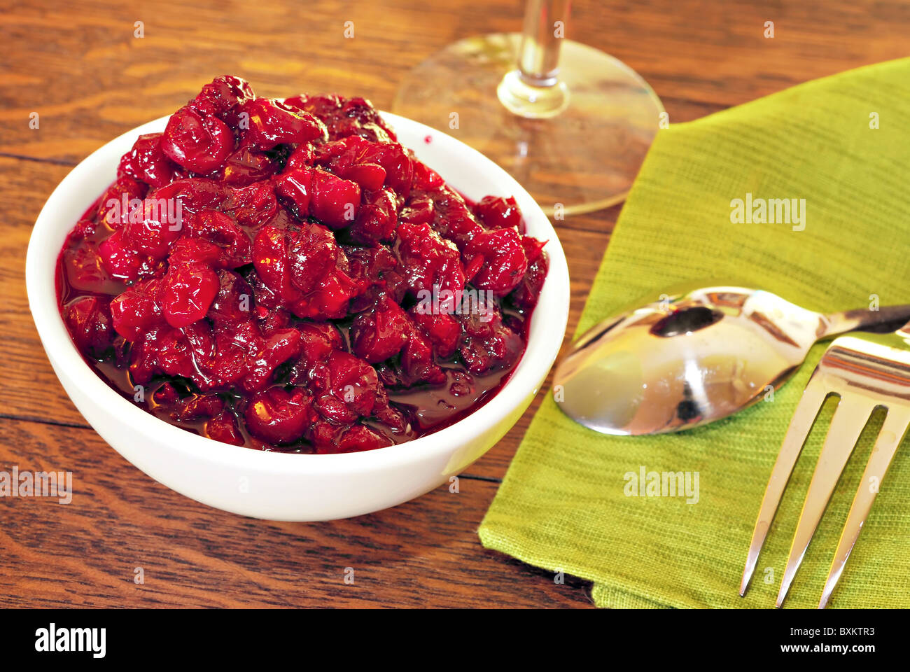 Bowl of fresh cranberry sauce on oak dining table Stock Photo
