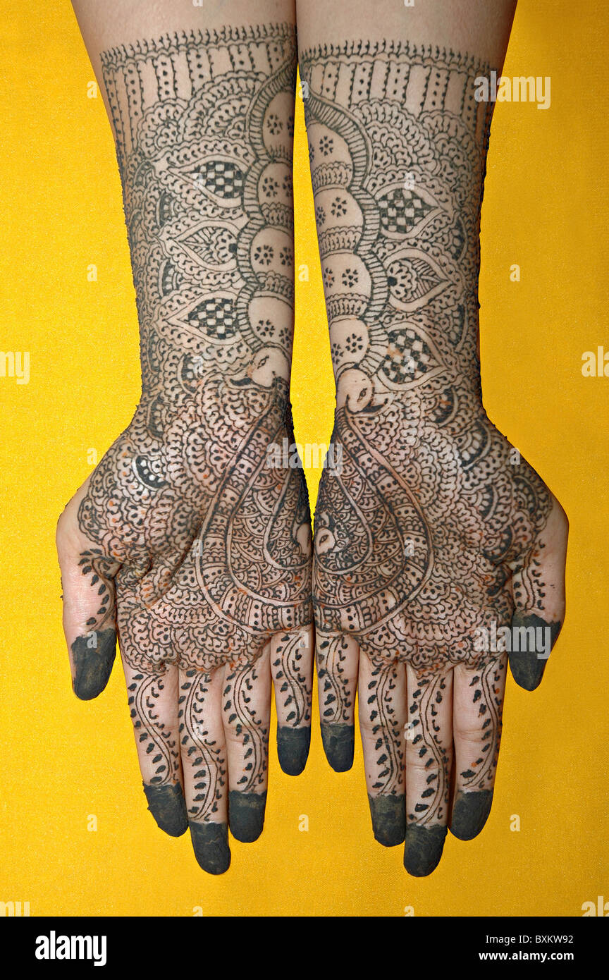Mehendi on hands covering palms and forehand. - Stock Image