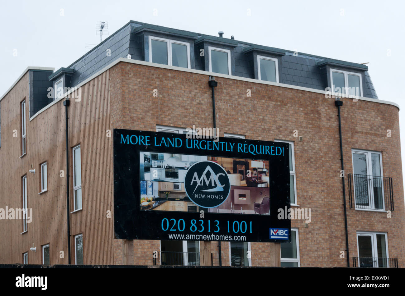 A sign saying 'More land urgently Required!' on a residential building site in South London. - Stock Image