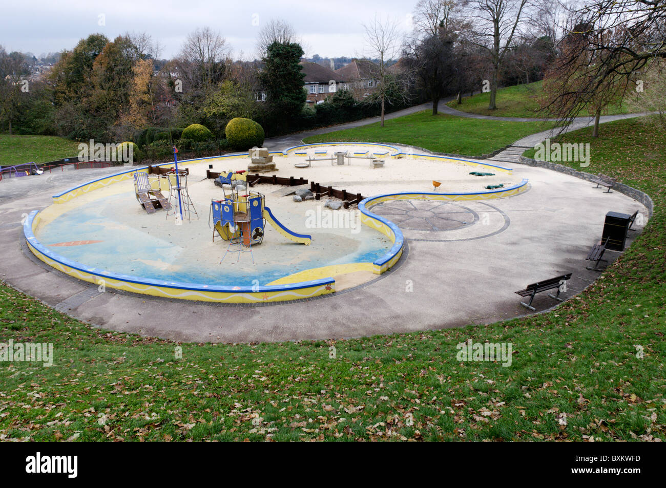 An empty and unused children's playground in a suburban park on a winter's day. - Stock Image