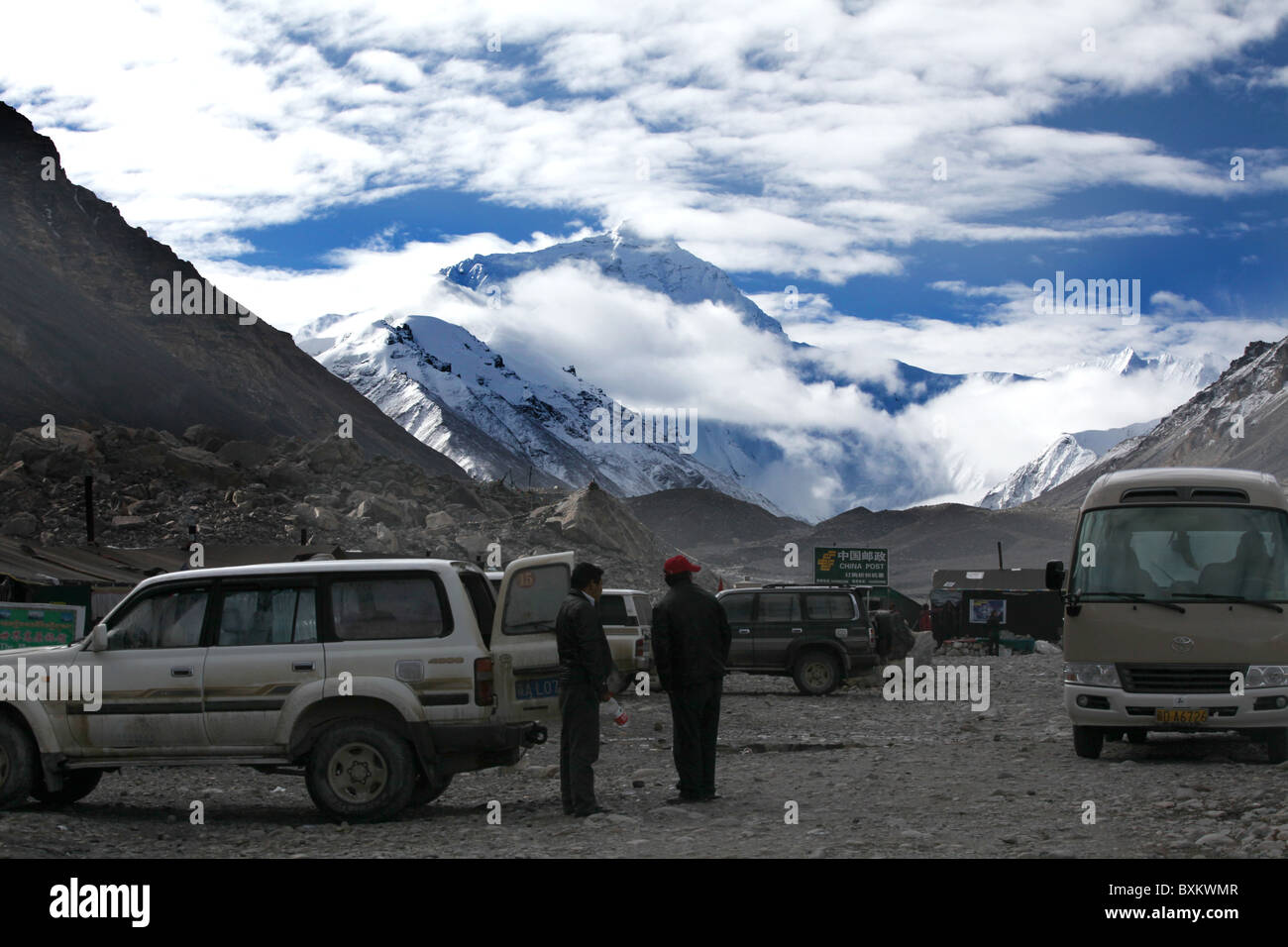 Tourist trucks at Everest Base Camp with a view of Everest or Qomolangma in Tibet, China. - Stock Image