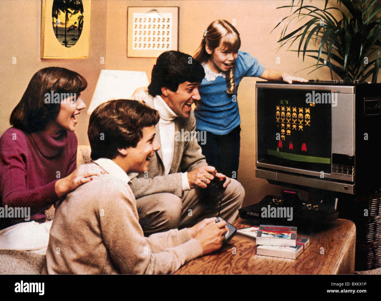 """games, video games, Atari 2600 Video Computer System, early video game, family with paddle playing """"Space Invaders"""", Stock Photo"""