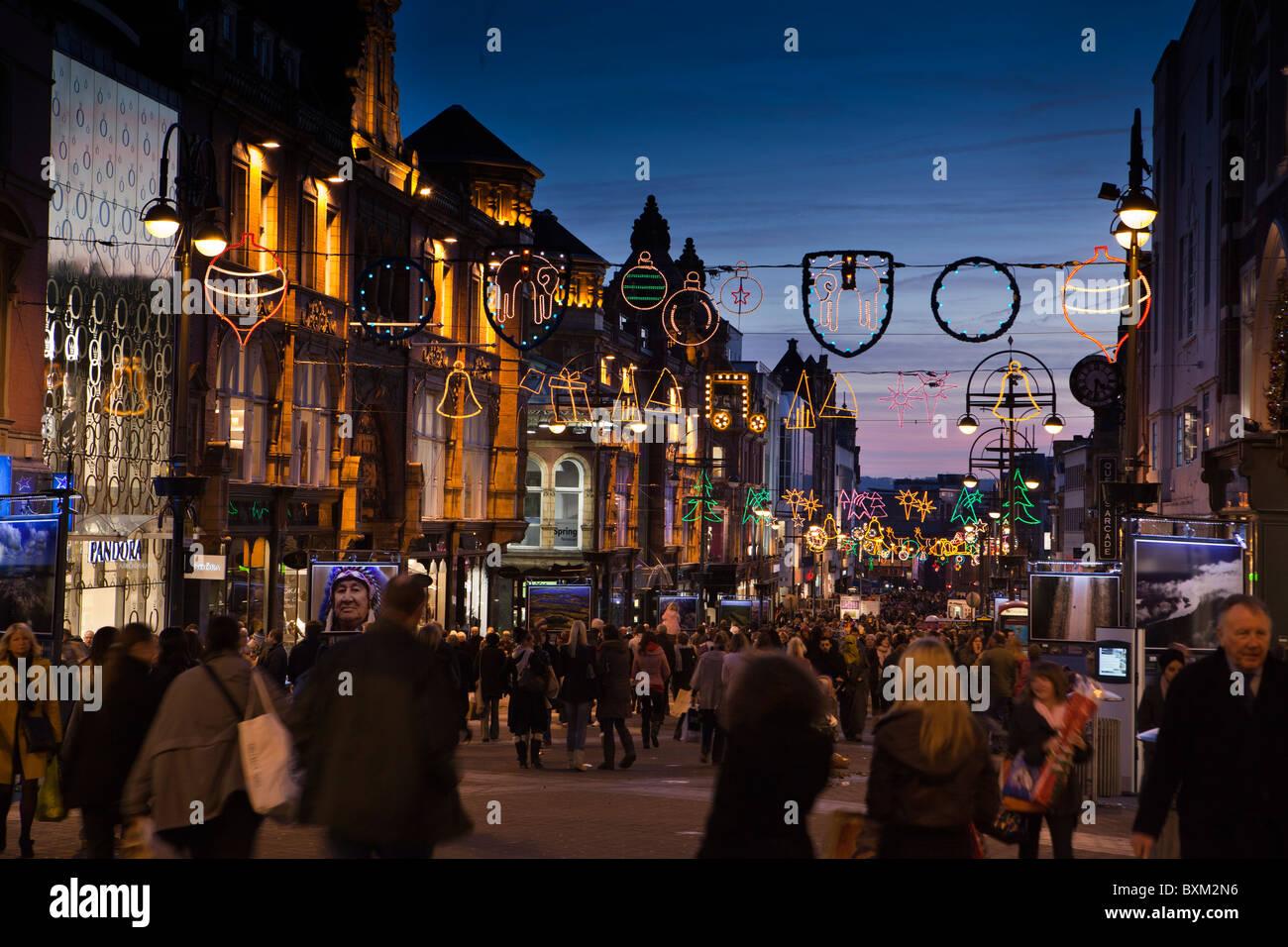 UK, England, Yorkshire, Leeds, Briggate, last minute shoppers below Christmas lights at dusk - Stock Image