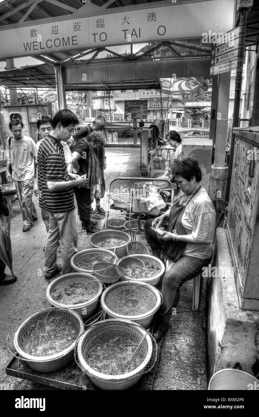 Tai O, Lantau Island, Hong Kong, China, Asia, Chines man buying live fish from lady on market stall - Stock Image