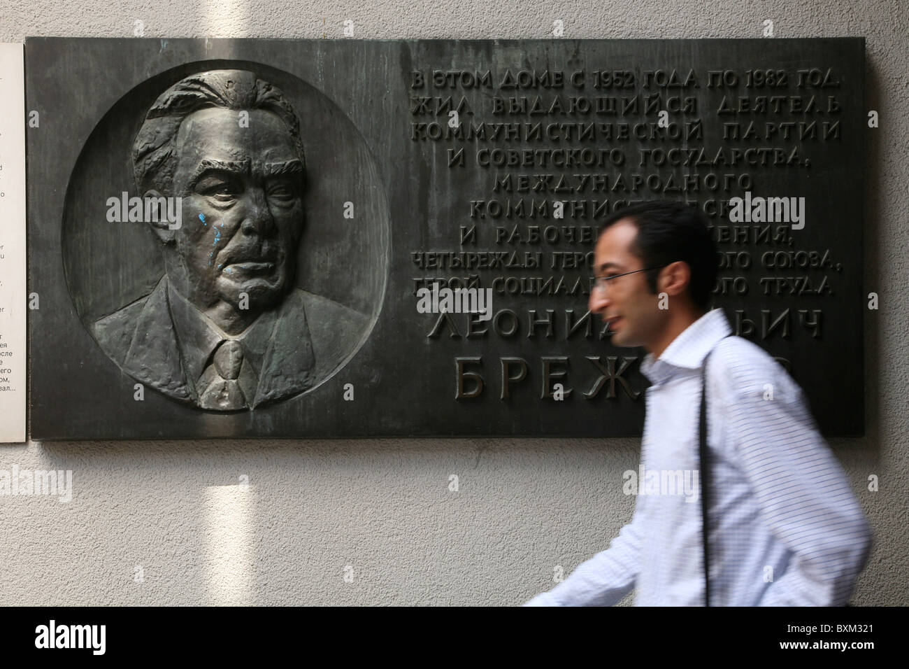 Man passing a commemorative plaque from the house of Leonid Brezhnev in Moscow in the Berlin Wall Museum in Berlin, - Stock Image