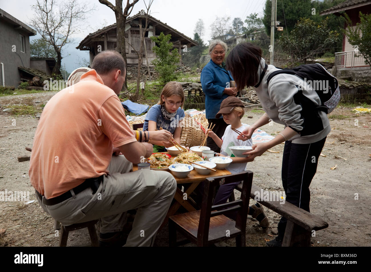A group of trekkers having lunch prepared in a small isolated village in west China. Stock Photo
