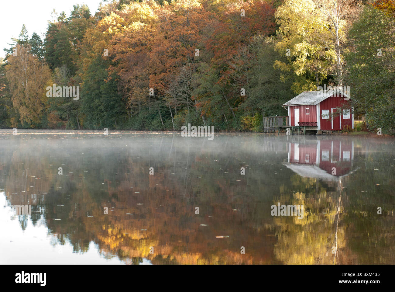 Seahouse sjöbod by lake Sävelången in fall 2010. swedish countryside red house with white stripes. - Stock Image