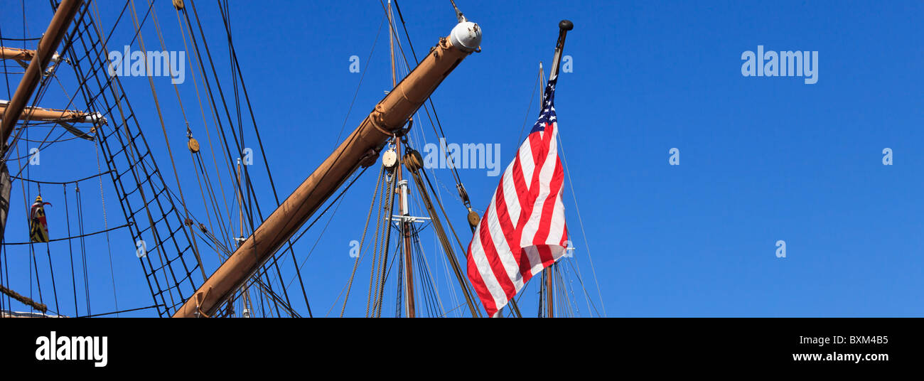 American flag and the rigging in the blue sky - Stock Image