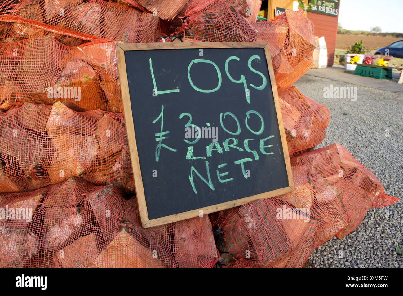 bags of logs for sale at a roadside farm shop, cornwall, uk - Stock Image