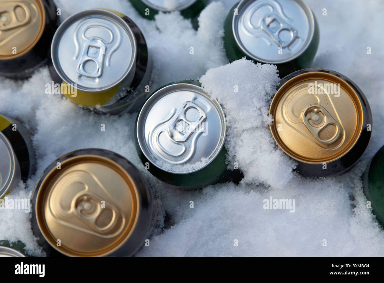 beer and alcohol cans buried in snow to keep them cool outdoors during winter - Stock Image