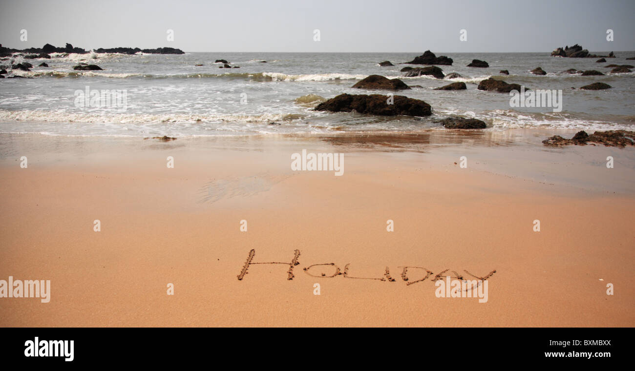 Holiday written in the sand on the beach, Goa - Stock Image