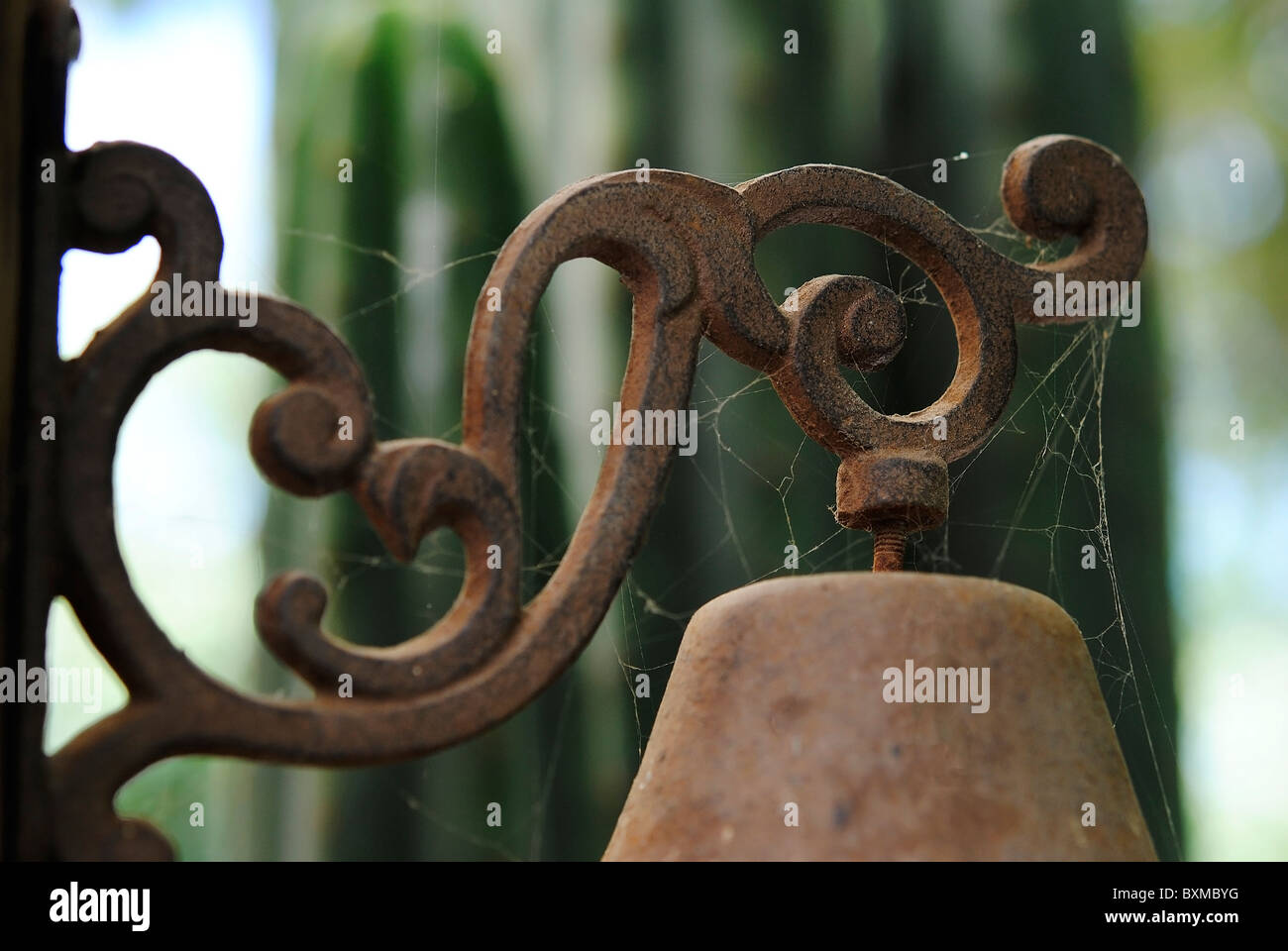 Black wrought iron, adornment that green color supports a bell, bottom. - Stock Image